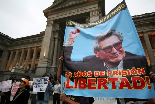 Members of MOVADEF hold a poster of Shining Path leader Abimael Guzman during a protest in front of the Justice Palace in Lima on, July 25, 2012